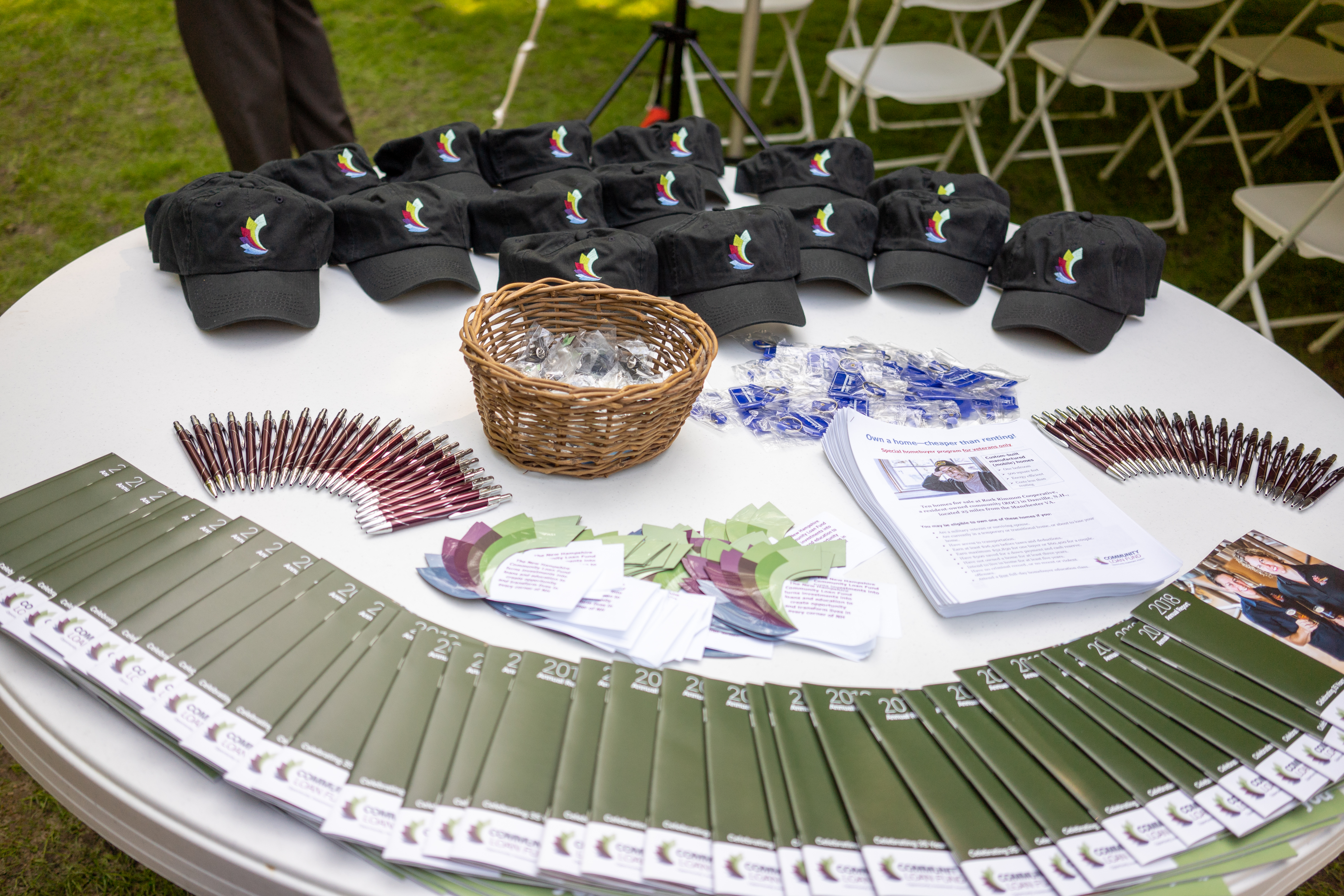 Giveaway items--hats, magnets, and annual reports--spread out on table