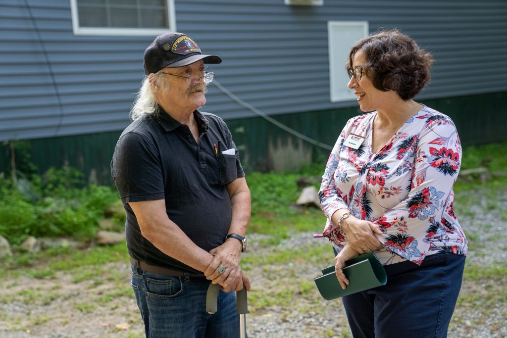 Jennifer Hopkins of the New Hampshire Community Loan Fund talks with Peter Searching Owl Giove, a U.S. military veteran