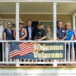 Congressman Chris Pappas poses with the Rock Rimmon board of directors and three veteran homeowners behind a sign that says Welcome Veterans