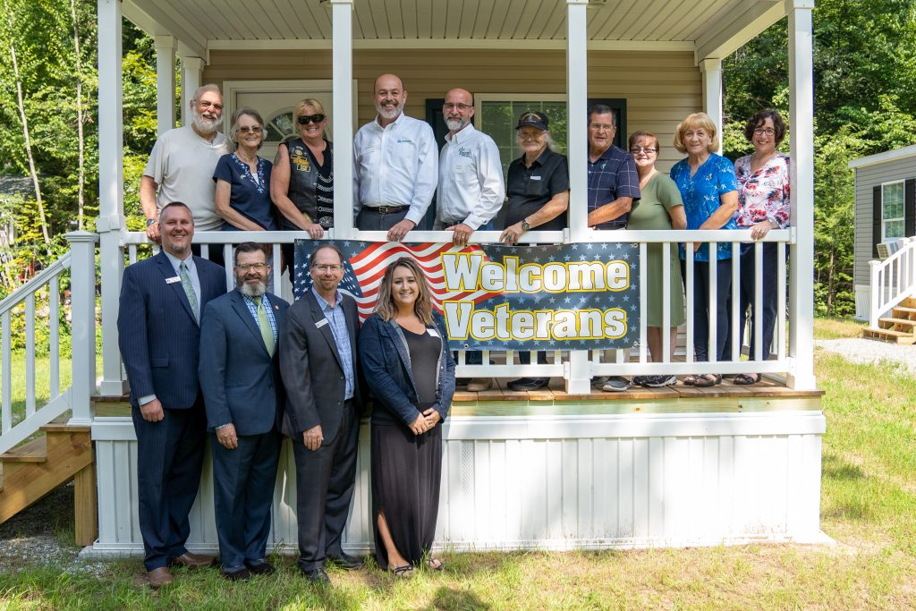 The Rock Rimmon board of directors, three veteran homeowners , and others posed with a sign that says Welcome Veterans