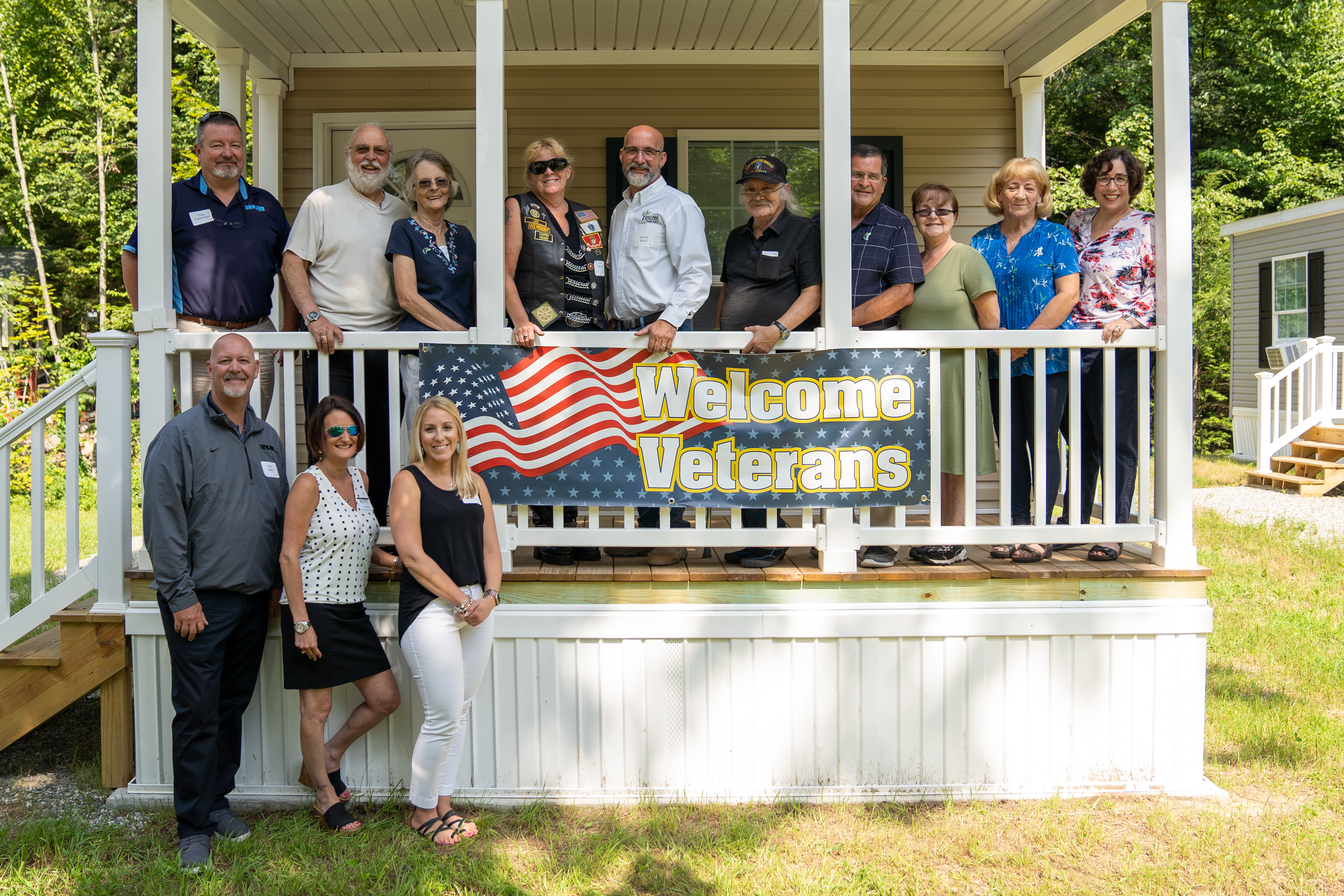 The Rock Rimmon board of directors, three veteran homeowners , and others posed behind a sign that says Welcome Veterans