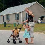 Mom and toddler pushing stroller wave at camera