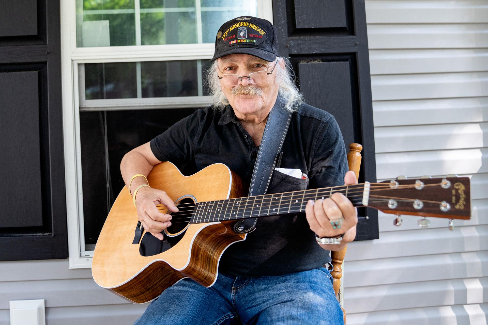 Grey-haired man playing guitar