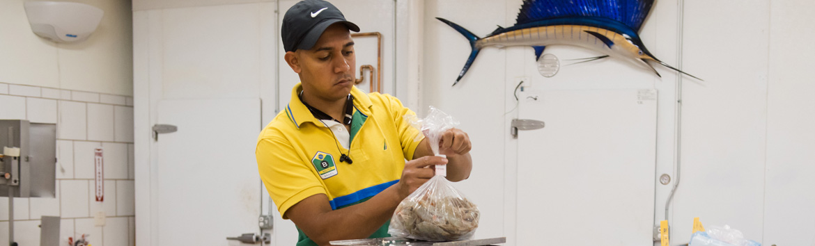 Man working at a market's fish counter