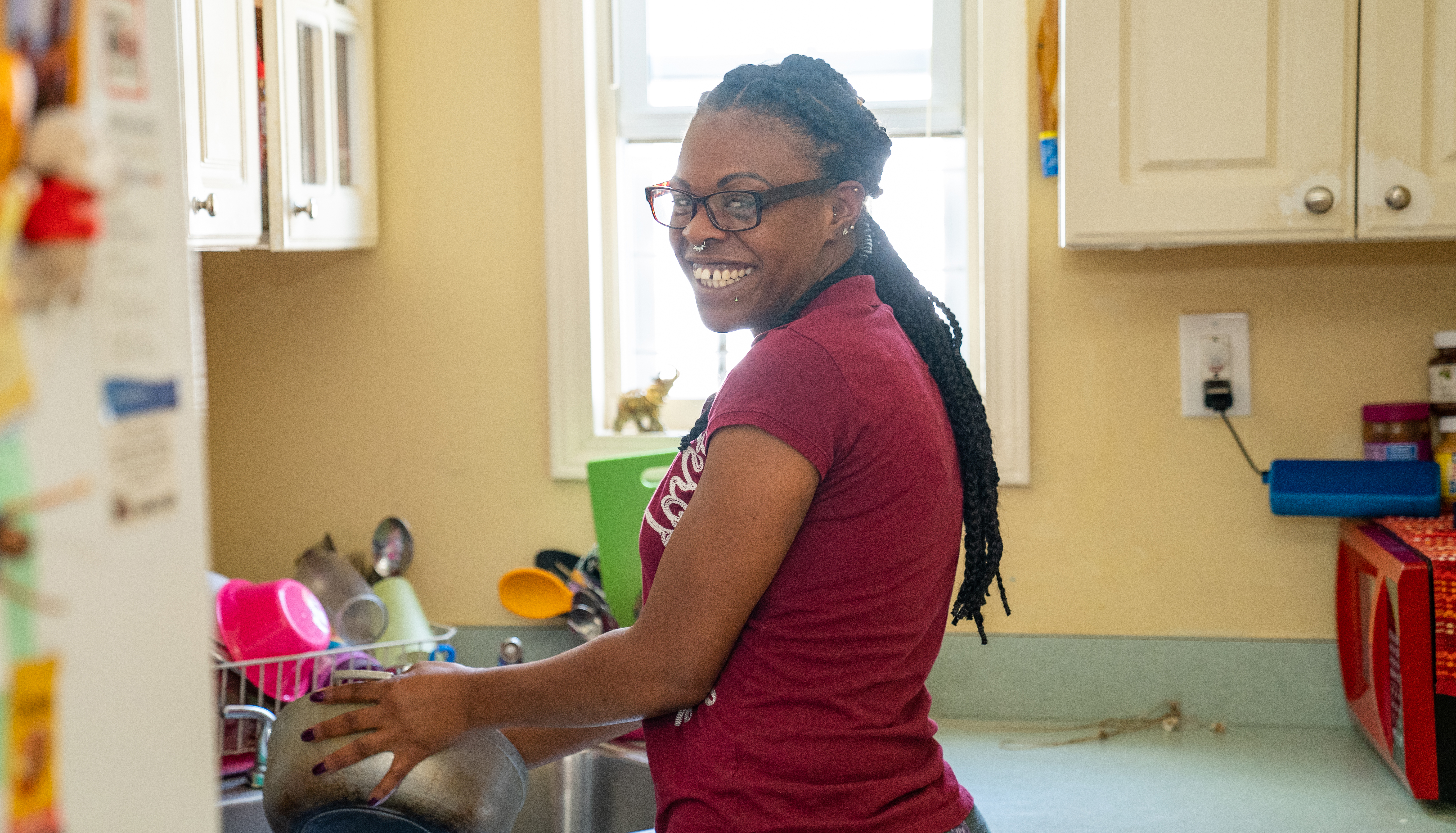 woman smiling while doing dishes