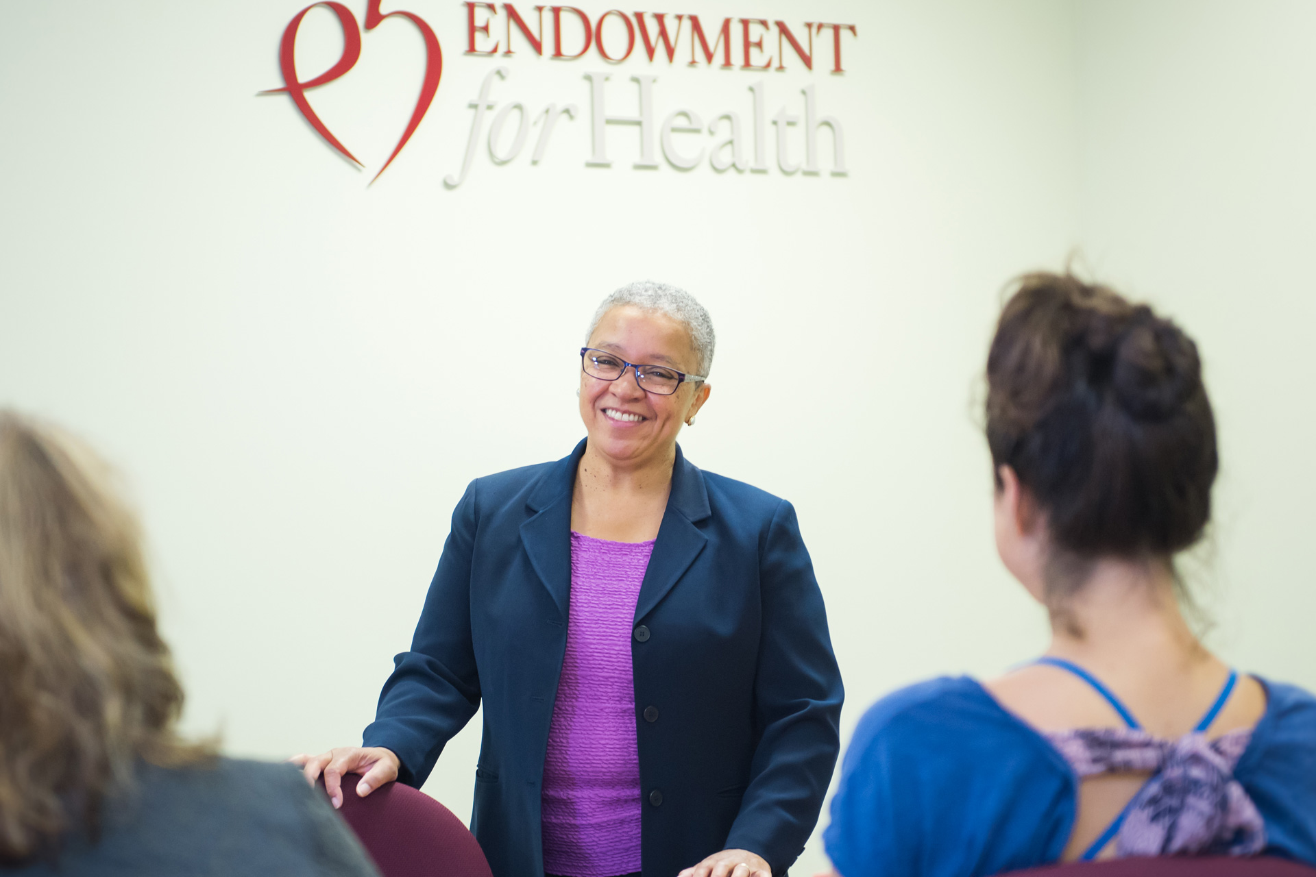 Woman stands below Endowment for Health logo