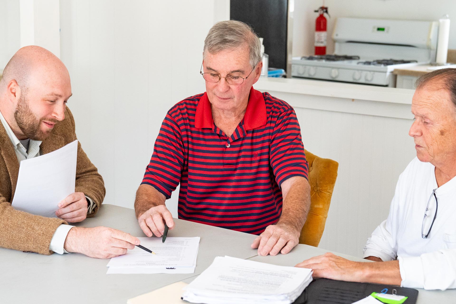 Three men meet around table