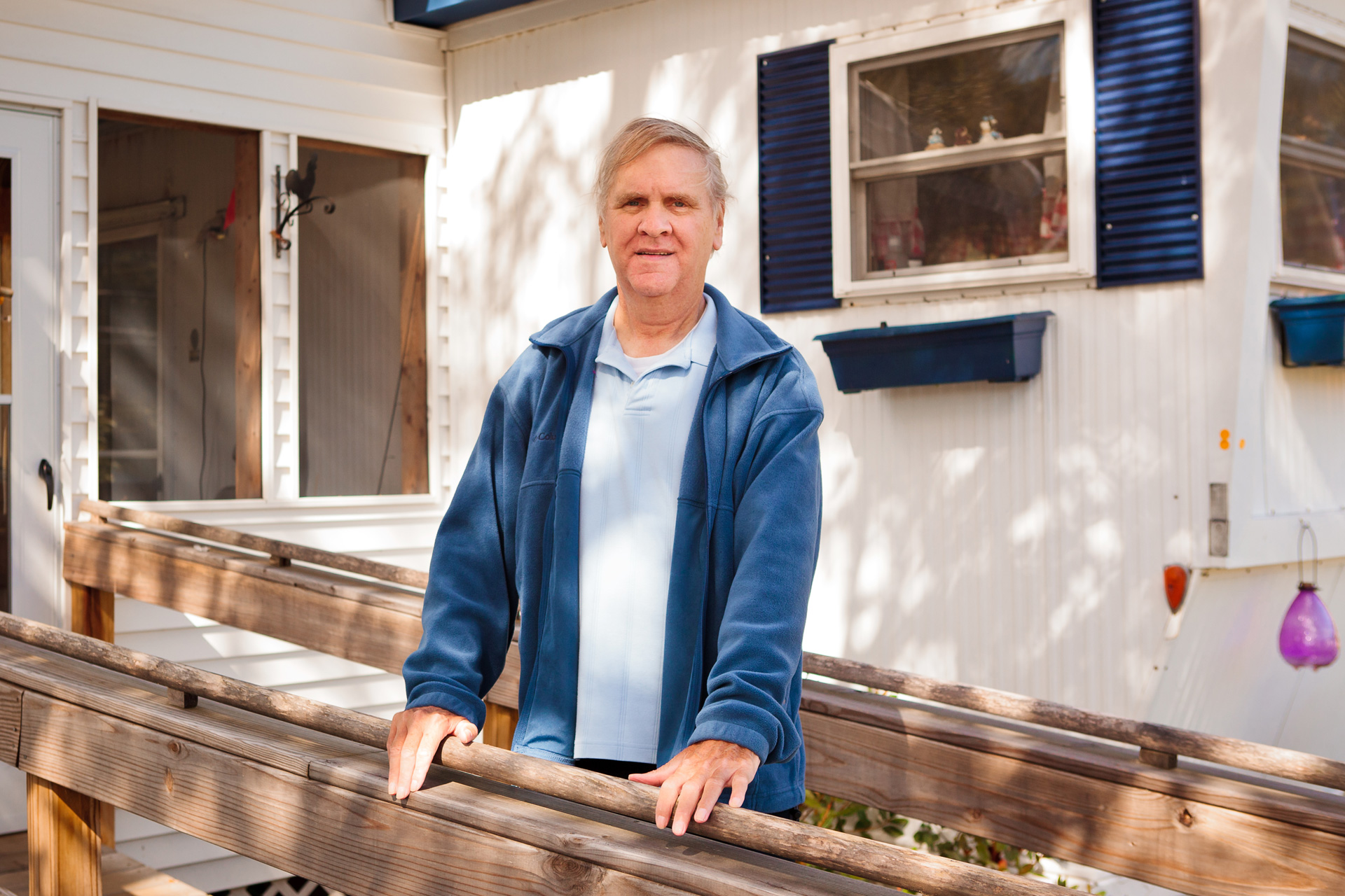 Man standing on porch, holding railing