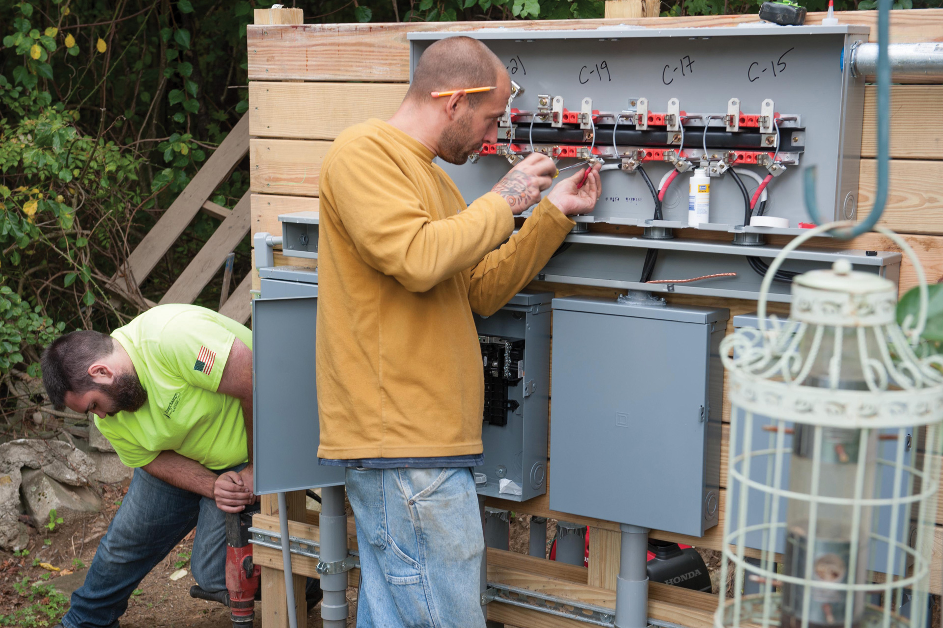 Two men install an electrical panel