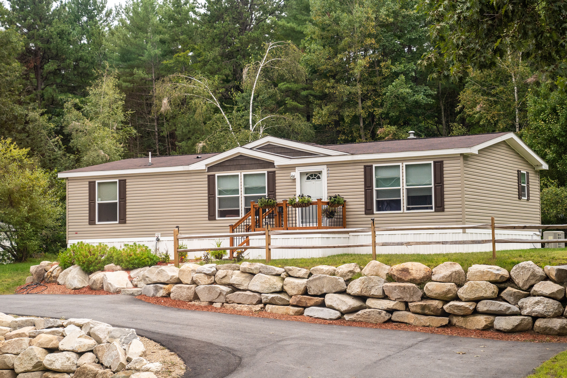 Modern manufactured home with stone wall and rail fence