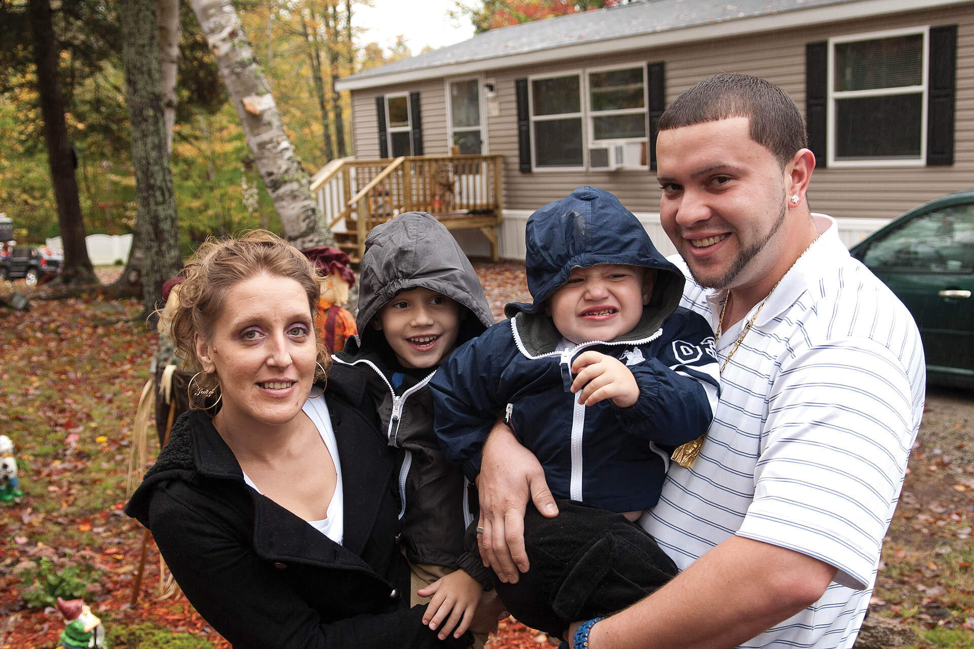 Couple holding two young children stand outside the home they bought with a Welcome Home Loan