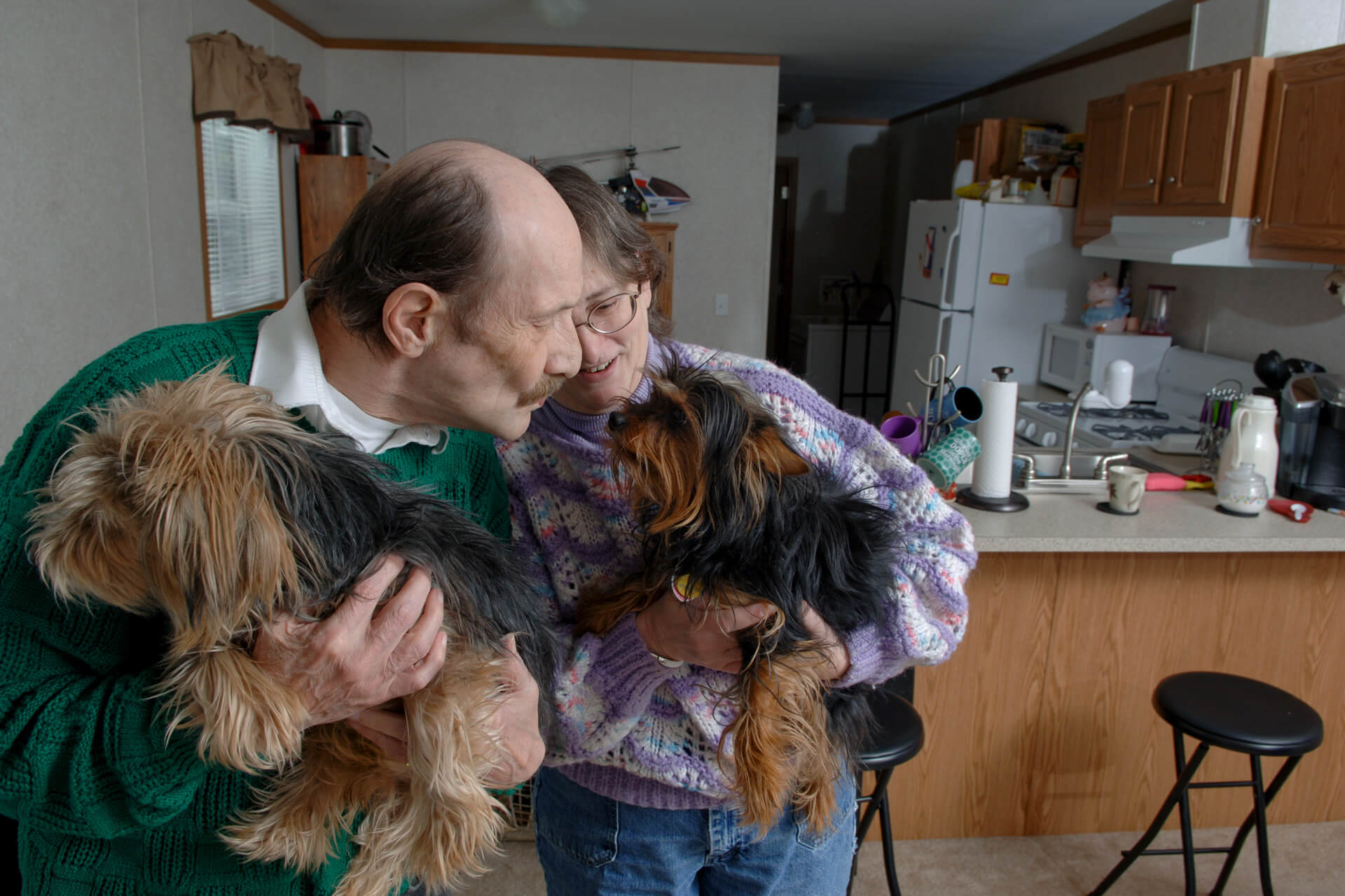 Man and woman holding squirmy dogs in kitchen