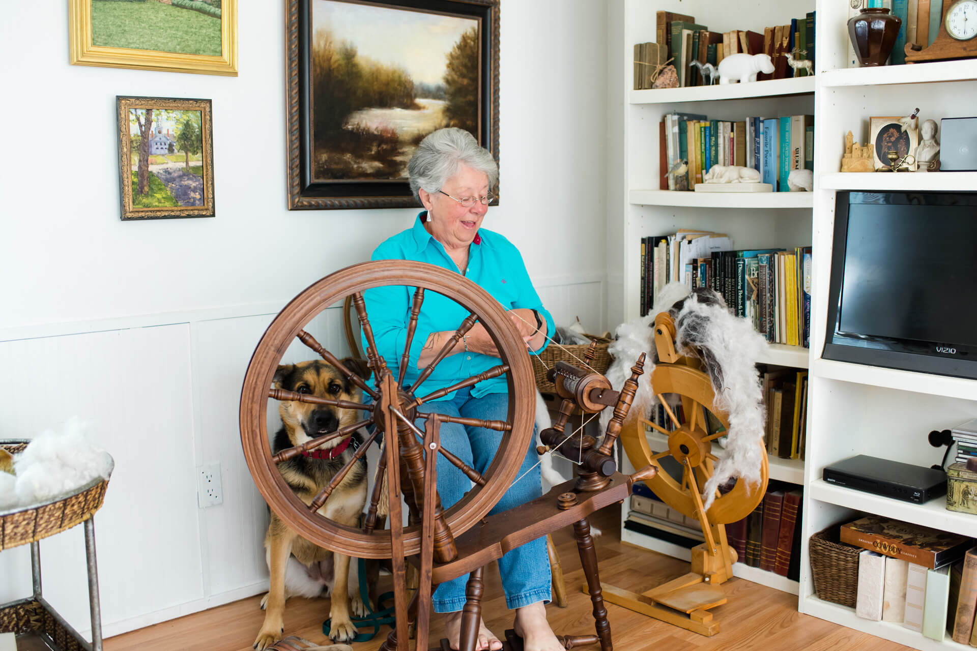 Woman spins yarn in her living room as her dog sits close by