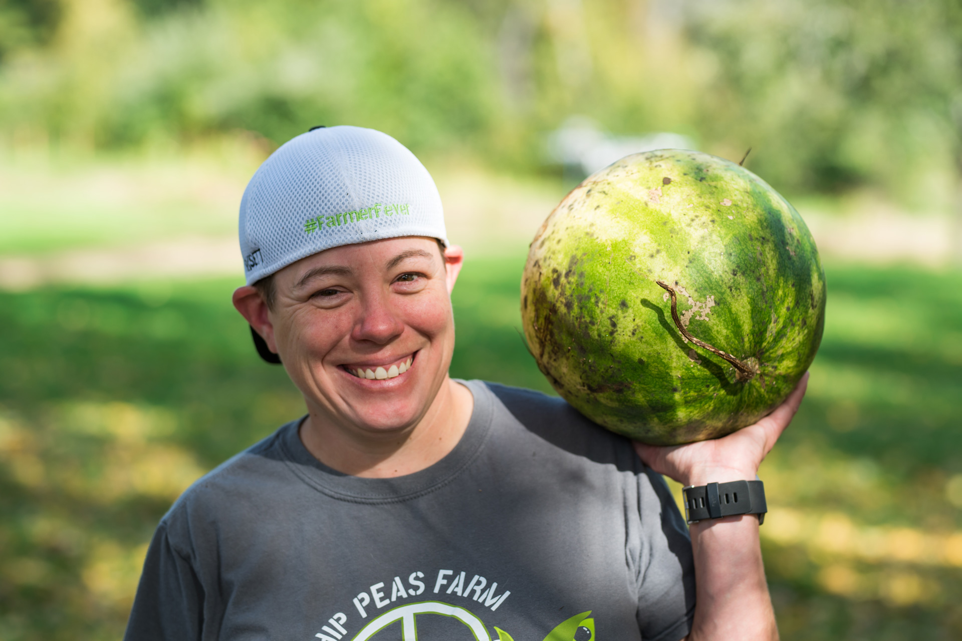 Young woman at farm hefts a large watermelon