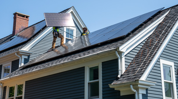 A worker installs solar panels on a rooftop