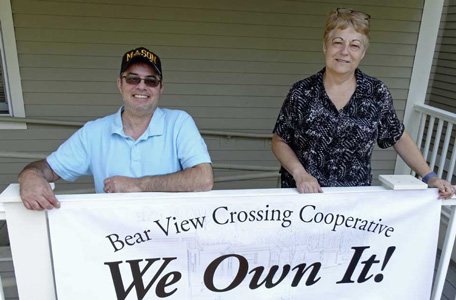 Board members of Bear View Crossing co-op hoist the We Own It sign.