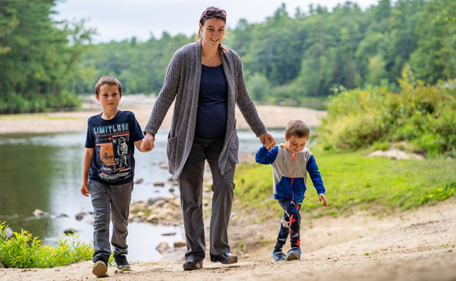 A woman walks for her two sons at the beach at Black Bear Village Cooperative in Conway, N.H.