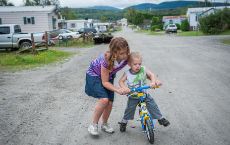 A girl helps her little brother ride a bike in Colebrook Homeowners Cooperative
