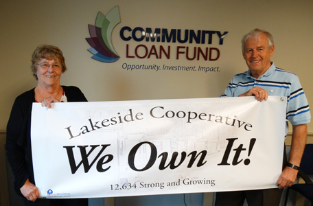 Lakeside Cooperative board members hold a We Own It banner after purchasing their park.
