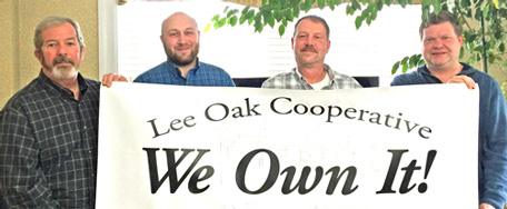 Lee Oak board members hold a We Own It sign at their closing