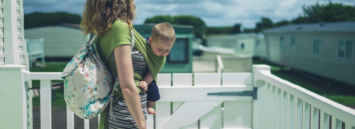A mom stands on the deck of her manufactured home with her baby in a green pouch and a diaper bag over her shoulder.