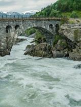 A rushing river runs under a granite bridge