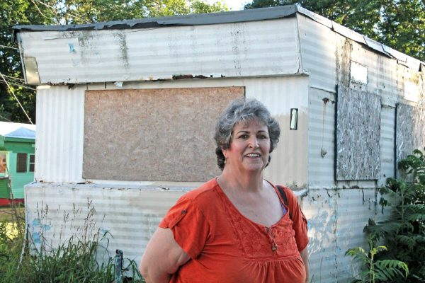 Woodbury Cooperative's Board President Leslie Williams, in front of an abandoned home that needs to be removed.