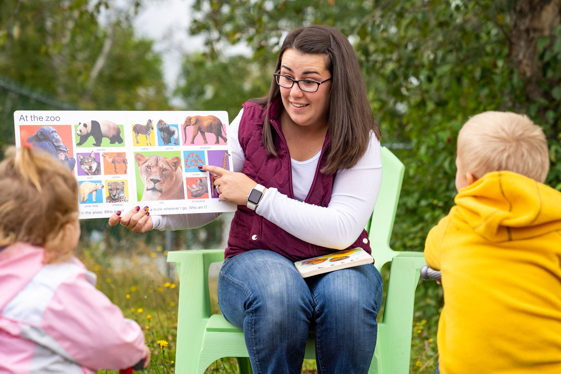 A teacher at Colebrook's Country Day School reads a picture book with a couple of toddlers.