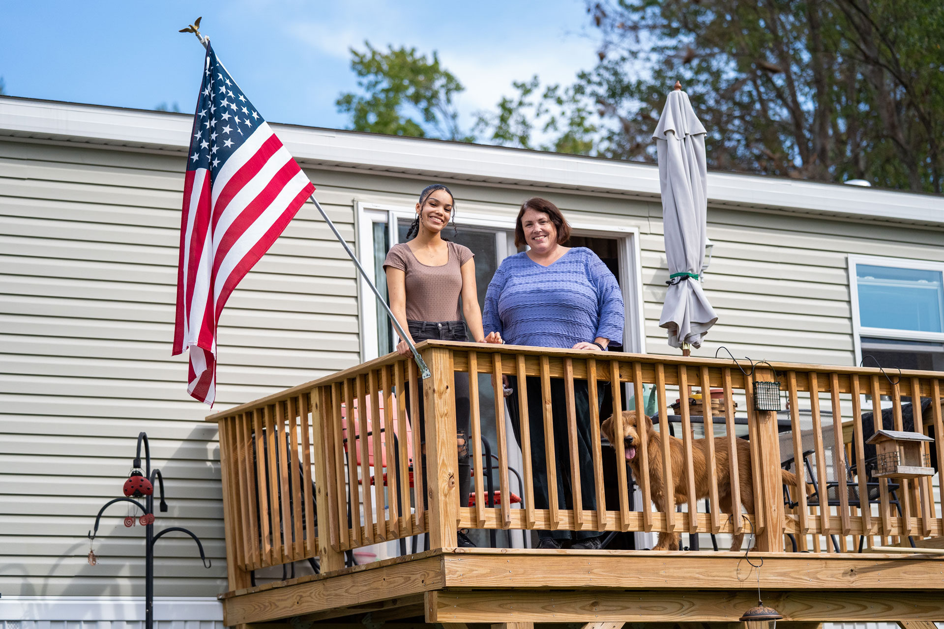 Jenn McLachlin and her daughter on the deck of their affordable manufactured home.