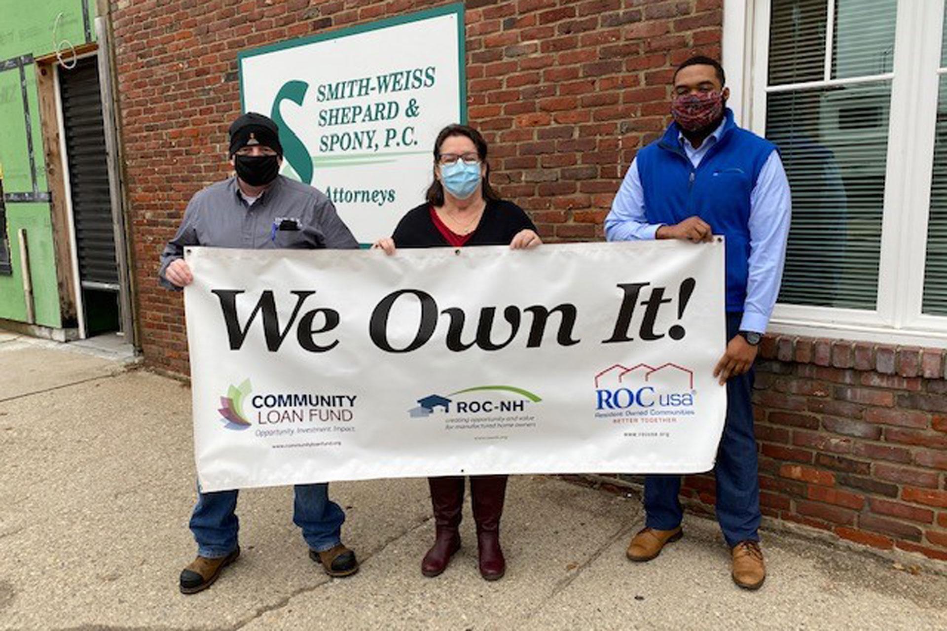 Two Jewel Estates board members hoist the co-op's We Own It banner.
